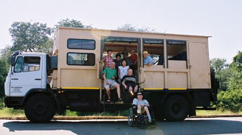 The group poses with Terry and Betty and the accessible safari truck